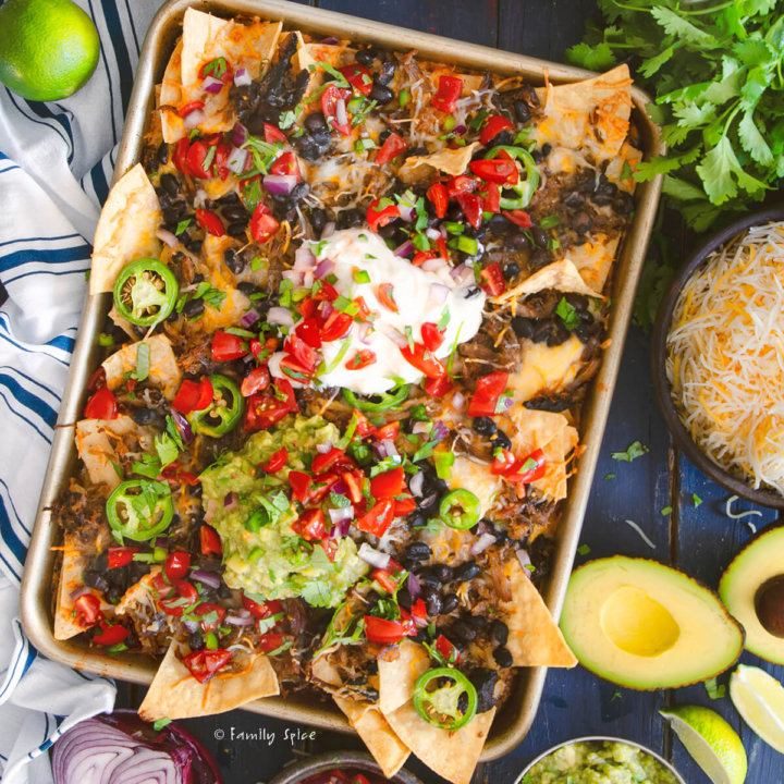 Overhead shot of sheet pan leftover pulled pork nachos surrounded by ingredients by FamilySpice.com