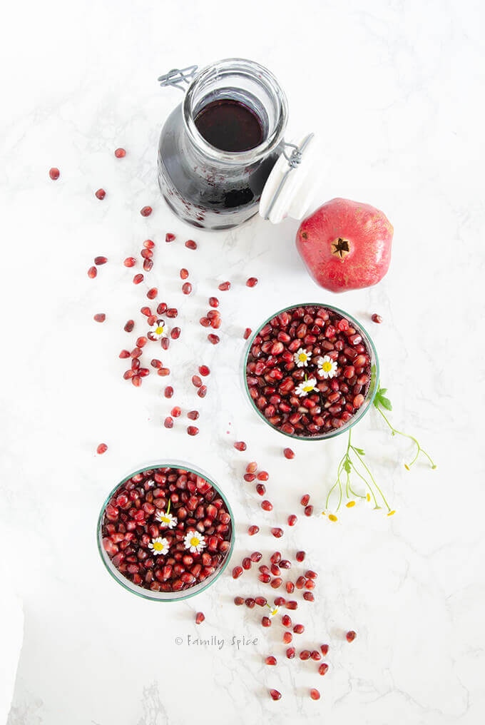 Overheard view of two glass containers with pomegranate gelatin and topped with pomegranate arils by FamilySpice.com