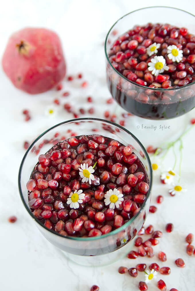 Closeup of two glass containers with pomegranate jello and topped with pomegranate arils by FamilySpice.com