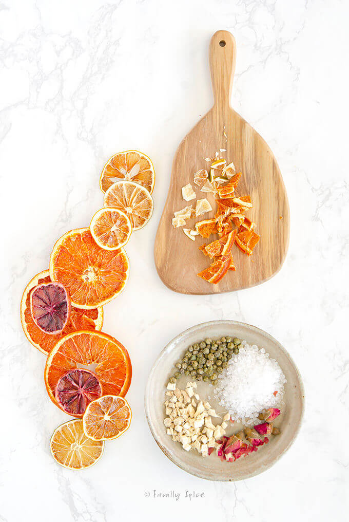 A cutting board with chopped dried oranges, a shallow bowl with coarse sea salt, green pepper corns, dried ginger and dried roses with assorted dried citrus slices by FamilySpice.com