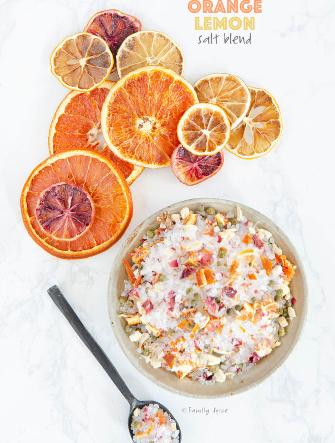 Overhead shot of a bowl and spoon filled with orange lemon salt blend with assorted dried citrus slices by FamilySpice.com
