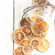 A large glass mason jar tipped over with oven dried lemon slices spilling out