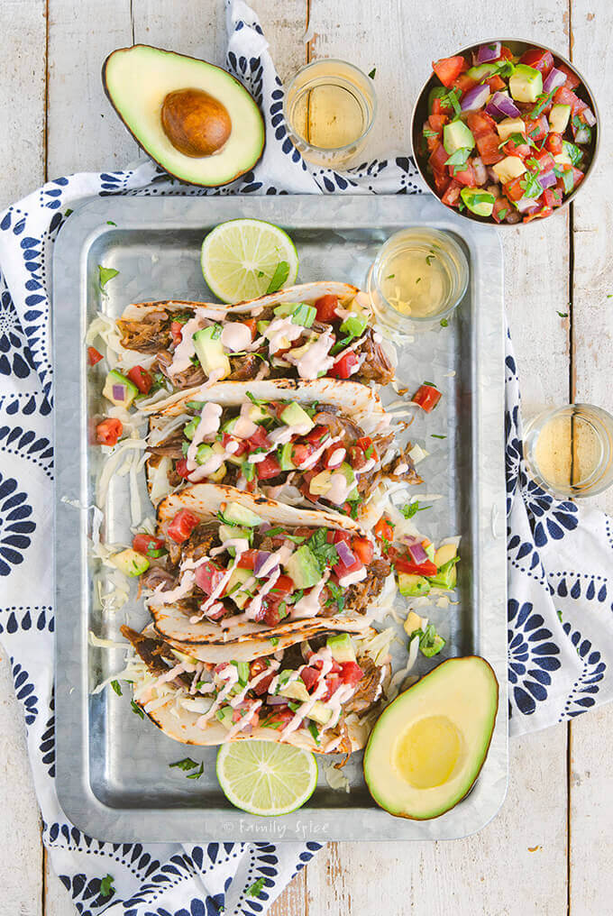 Top view of pulled pork tacos in flour tortillas on a metal tray with spicy crema by FamilySpicecom