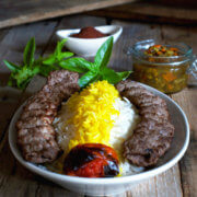 A plate full of basmati rice with saffron and koobideh kabob with roast tomatoe, sumac, herbs and torshi