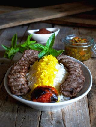 A plate full of basmati rice with saffron and koobideh kabob with roast tomatoe, sumac, herbs and torshi