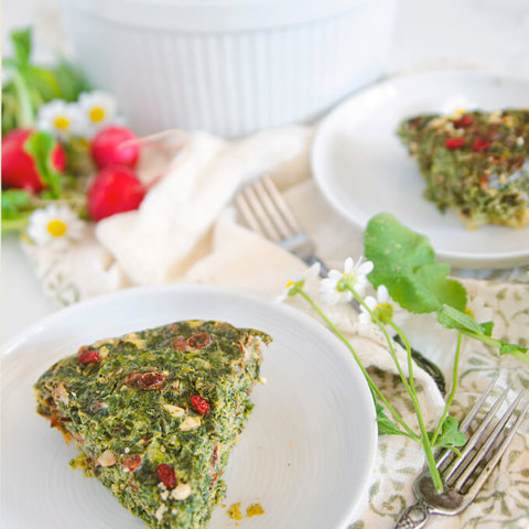 A slice of kuku sabzi on a white plate with radishes and more dishes behind it by FamilySpice.c