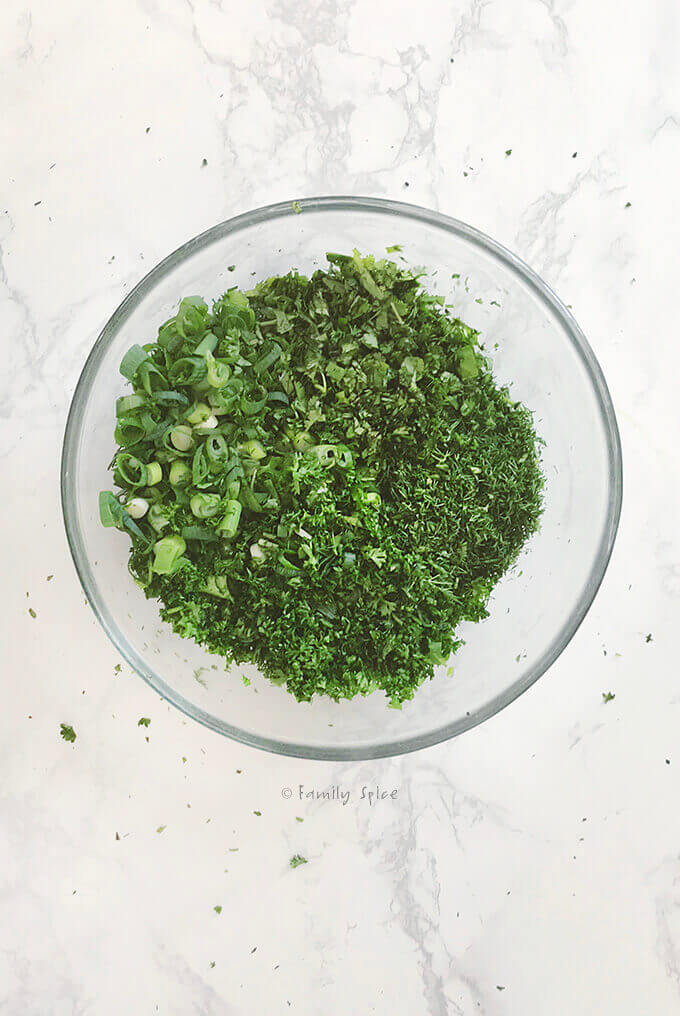 A bowl full of chopped herbs for kuku sabzi by FamilySpice.com