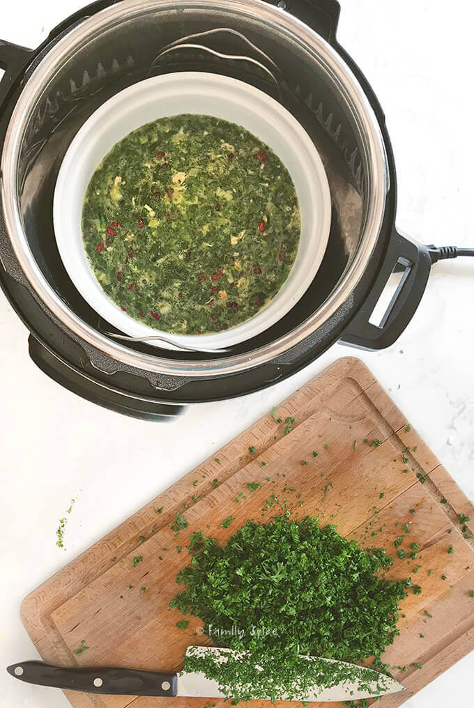 Overhead shot of an instant pot holding Persian kuku sabzi and fresh chopped herbs by FamilySpice.com