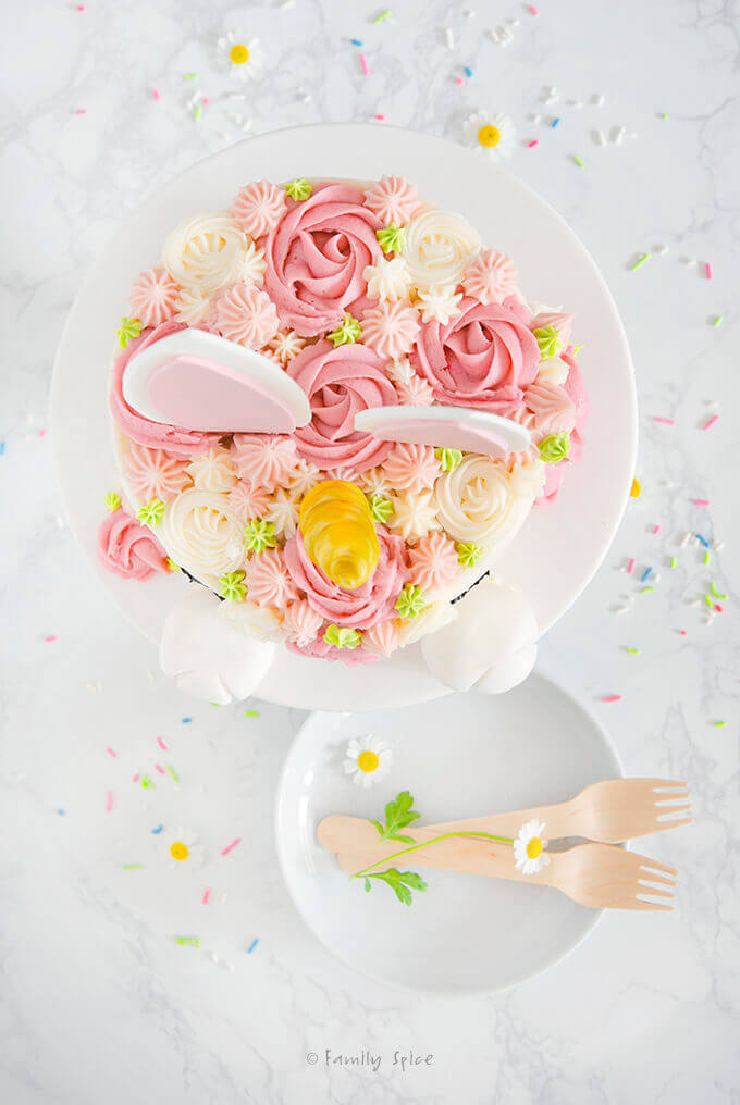 Top view of a white cake frosted with dark pink rosettes, white rosettes and frosting accents in light pink with edible bunny ears and unicorn inserted in it plus a couple of white plates by FamilySpice.com