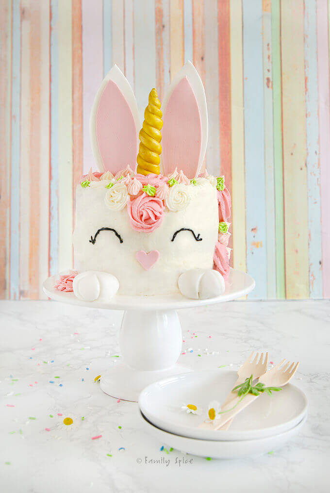 An Easter bunny unicorn cake in pink tones on white pedestal with small white plates by FamilySpice.com