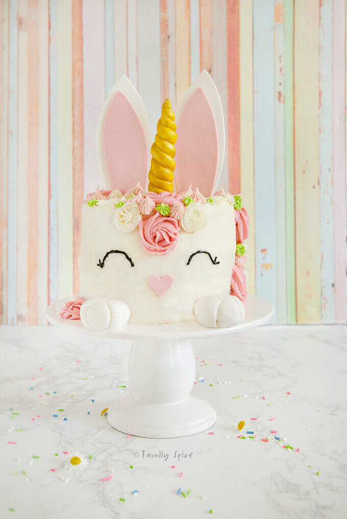 An Easter bunny unicorn cake with pink rosettes on white pedestal with pastel background by FamilySpice.com