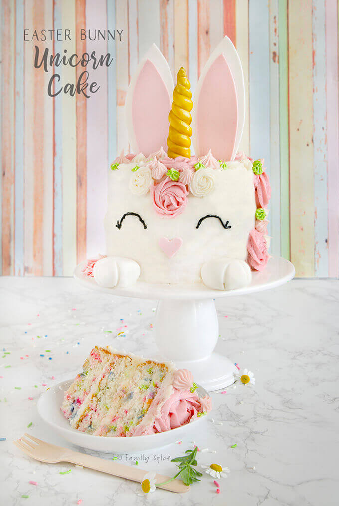 Easter bunny unicorn cake with pastel pink colors and a funfetti cake slice on a white plate by FamilySpice.com