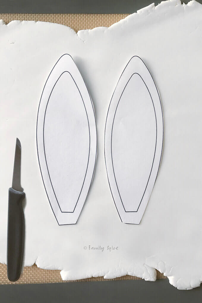 Bunny ear template placed on rolled out white gum paste and ready to be cut out by FamilySpice.com