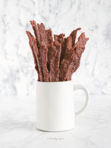 Side view of a white mug with sticks of ground beef jerky in it