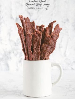 Sticks of ground beef jerky sticking out of a white ceramic mug by FamilySpice.com