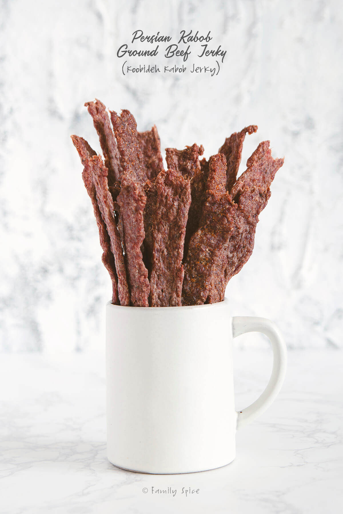 Sticks of ground beef jerky sticking out of a white ceramic mug by FamilySpice.com