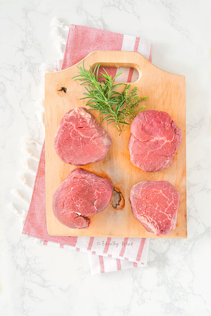 Four raw filet mignon steaks on a wood cutting board by FamilySpice.com