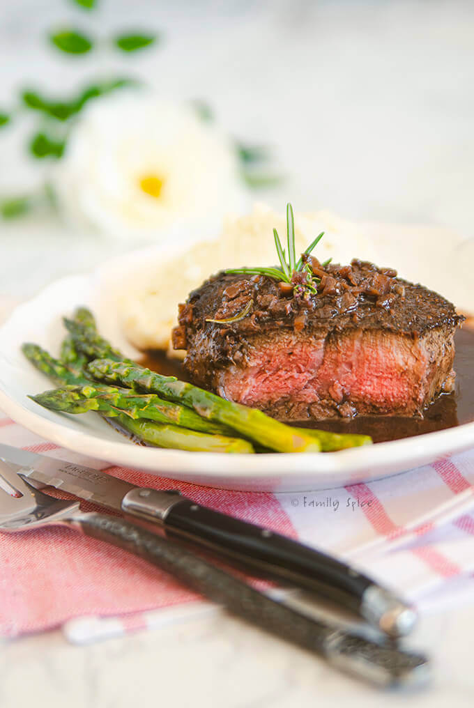 Closeup of a plate with a filet mignon cut open, asparagus and mashed potatoes by FamilySpice.com