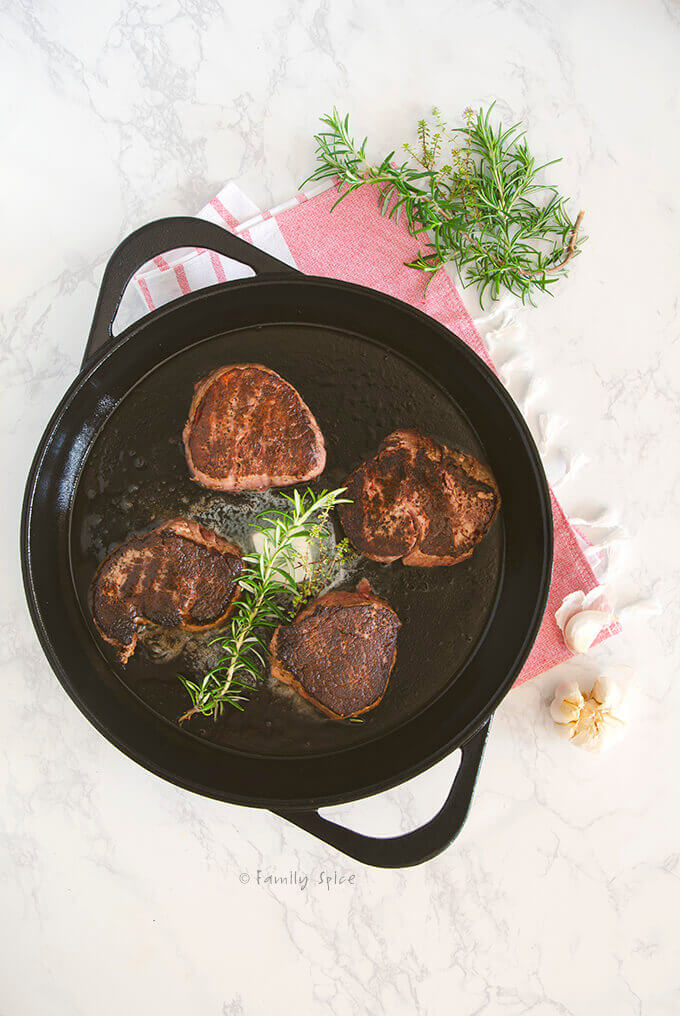 A large cast iron pan with seared filet mignons, melting butter and fresh herbs by FamilySpice.com