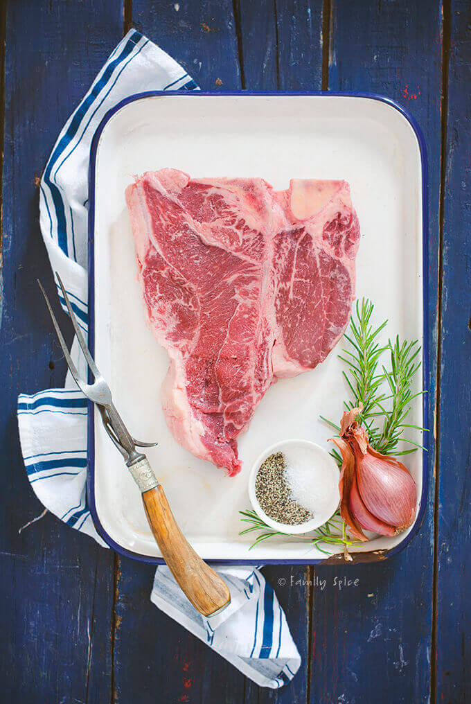 Overhead view of a raw porterhouse steak with salt, pepper, shallot and rosemary on a white enamel pan by FamilySpice.com