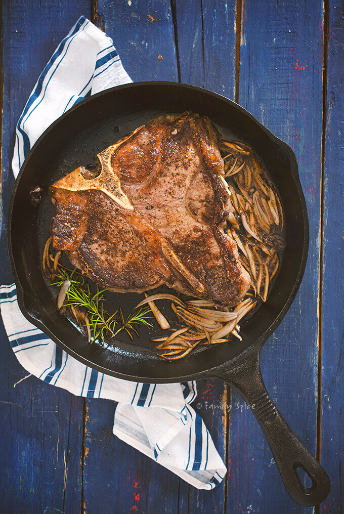 Overhead view of a pan seared porterhouse steak in a cast iron pan with rosemary and shallots by FamilySpice.com