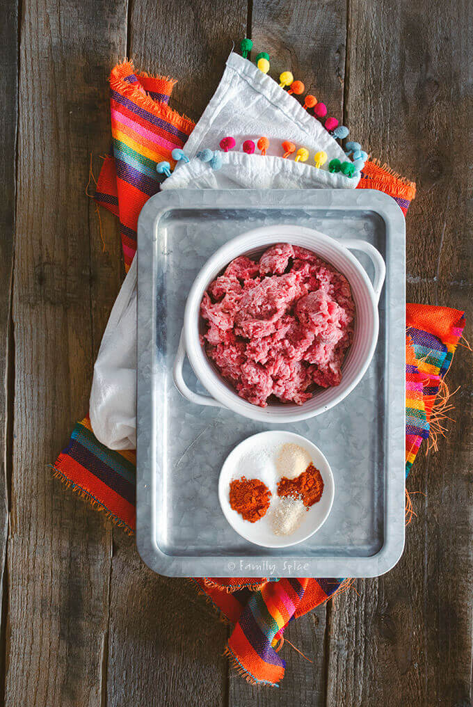 Top view of a stainless tray with a bowl of ground beef and a small plate with a variety of spices by FamilySpice.com