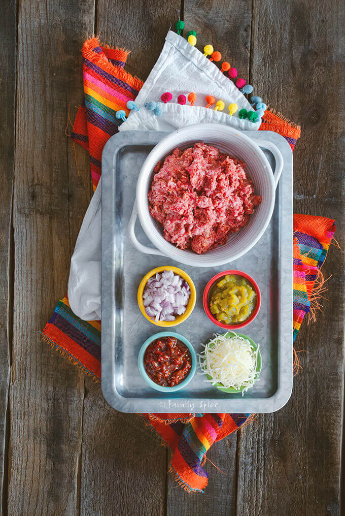 Top view of a stainless tray with ingredients to make queso stuffed burgers by FamilySpice.com