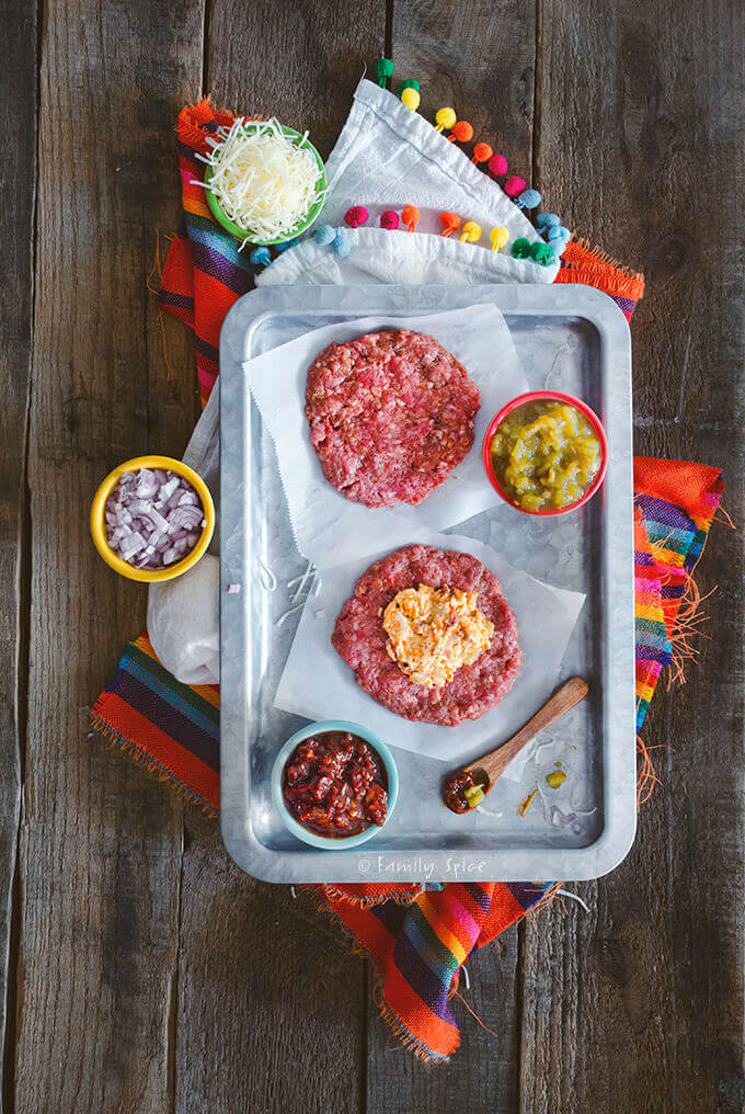 Top view of a stainless tray with two meat patties, one topped with a cheese stuffing with chiles and onions by FamilySpice.com