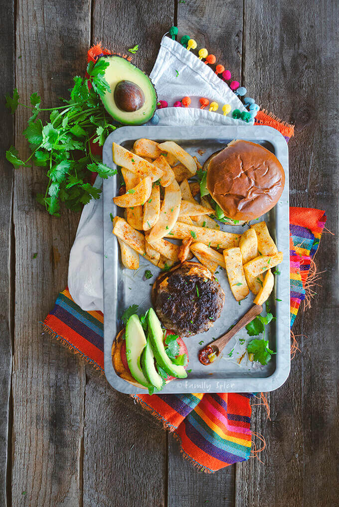 Top view of a stainless tray with two burgers, one with bun top on the side with avocado, cilantro and steak fries by FamilySpice.com