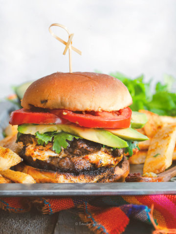 Side view of a queso stuffed burger with tomatoes, cilantro and avocado slices on a tray with fat steakhouse french fries