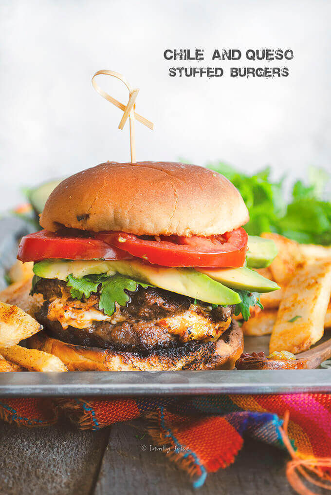 Closeup of a hamburger stuffed with queso oozing out surrounded by steak fries by FamilySpice.com