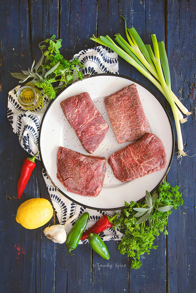 A round white platter with 4 raw flat iron steaks surrounded by fresh herbs, olive oil, lemon, garlic and peppers by FamilySpice.com