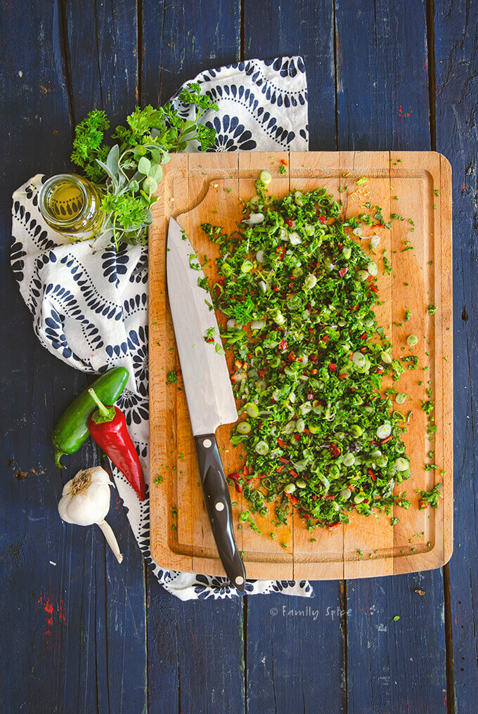 Fresh herbs, garlic and red jalapeño pepper chopped on a wooden cutting board by FamilySpice.com
