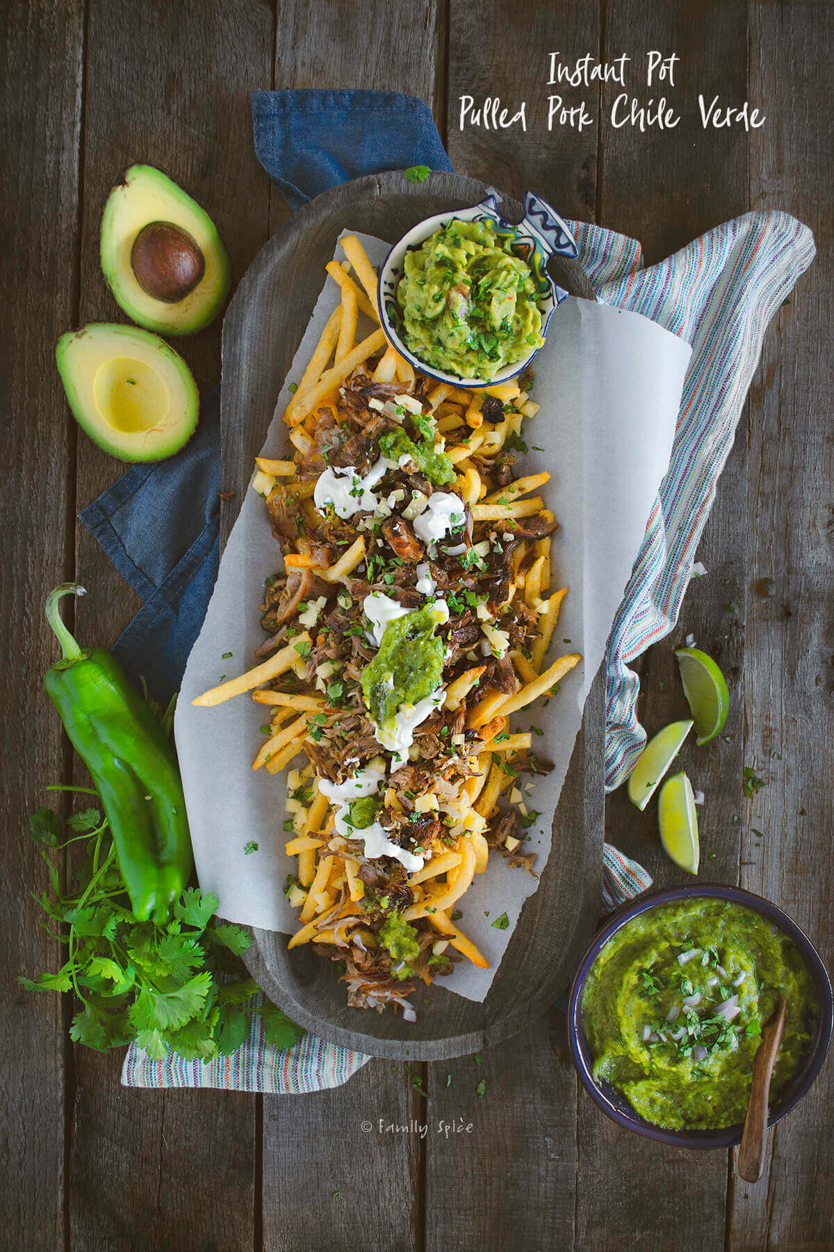 Overhead shot of a wooden tray filled with french fries topped with carnitas, sour cream and salsa verde by FamilySpice.com