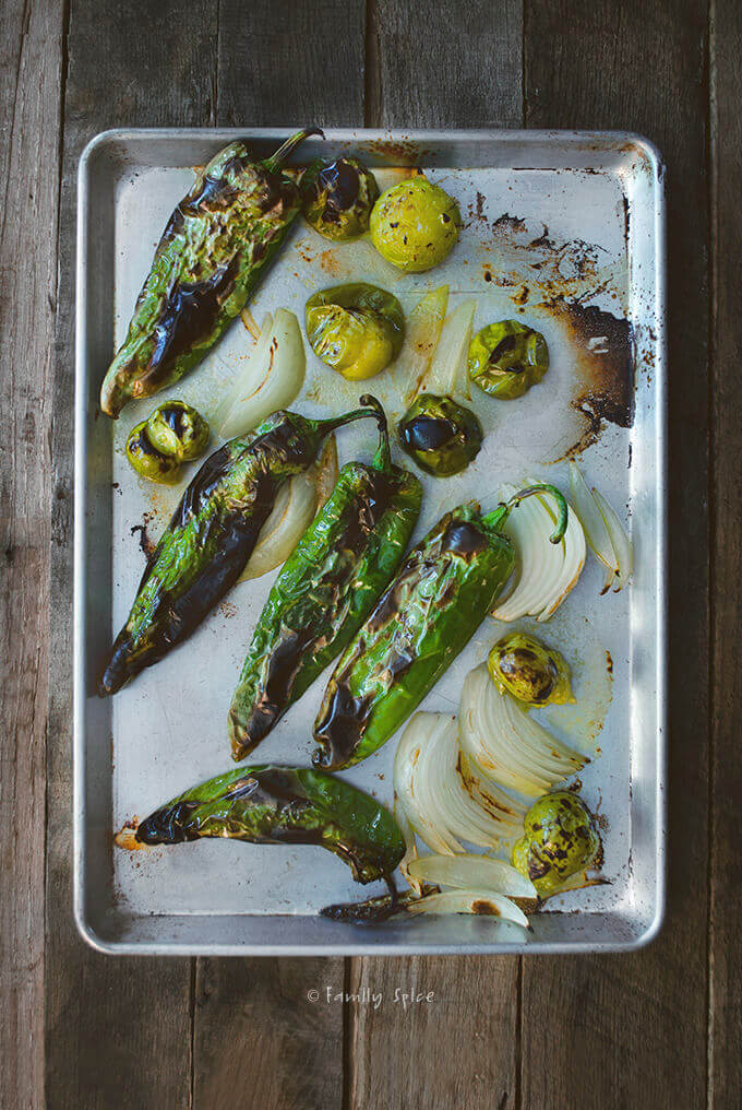 A baking sheet filled with roasted green chiles, tomatillos and onions by FamilySpice.com