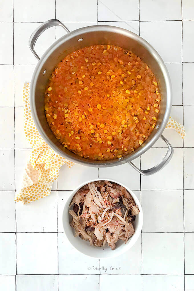 Overhead view of a pot filled with Spanish rice and a small bowl of shredded pulled pork by FamilySpice.com