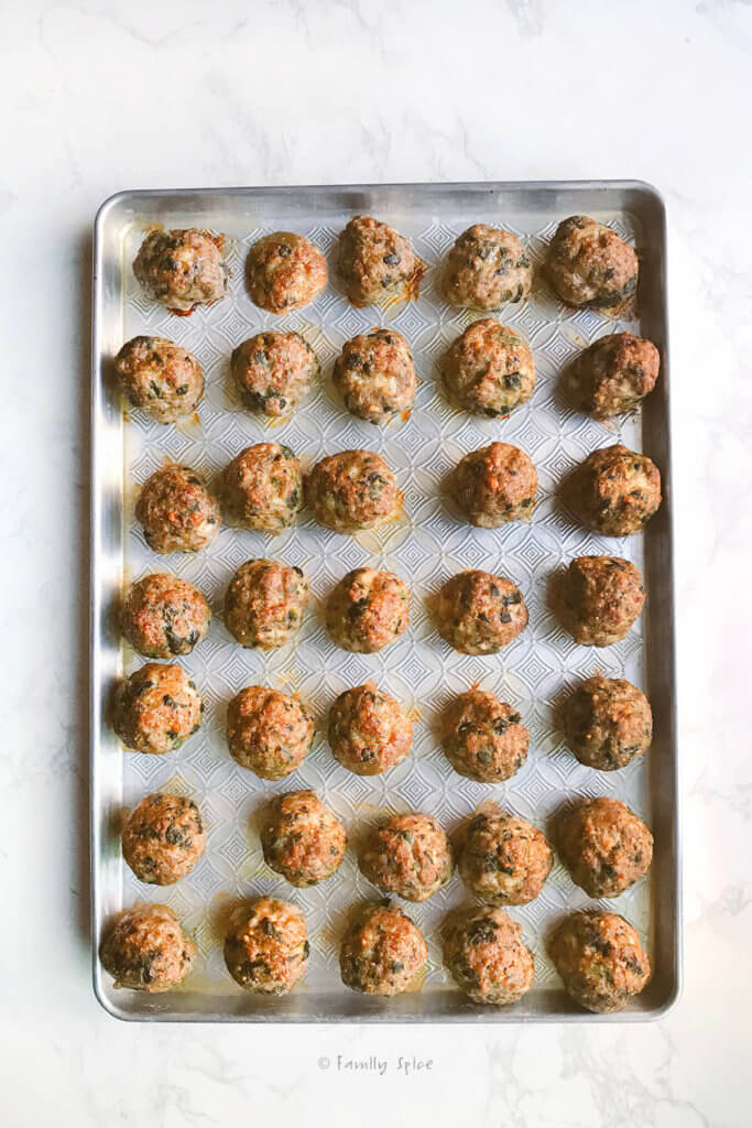 A baking sheet filled with baked meatballs
