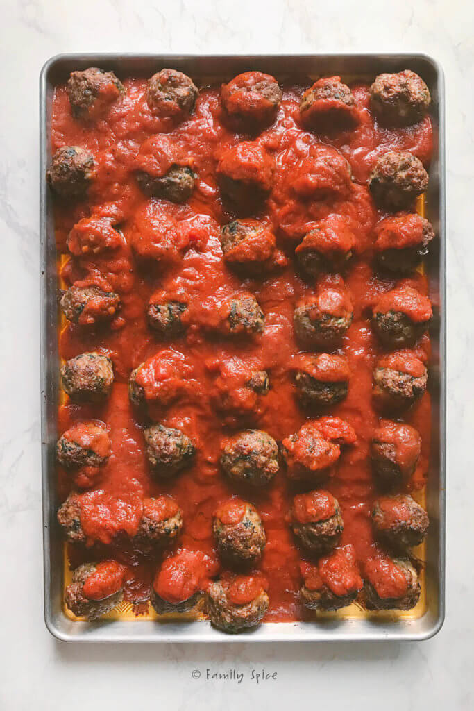 A baking sheet filled with baked meatballs and marinara sauce poured over it