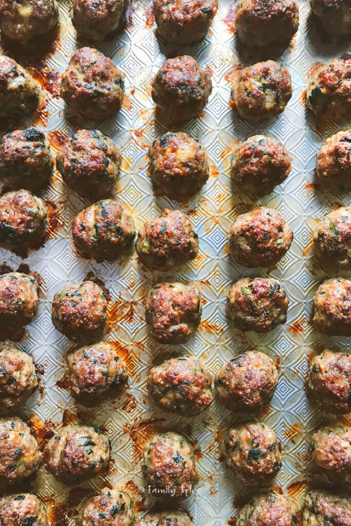 closeup of a baking sheet filled with baked meatballs