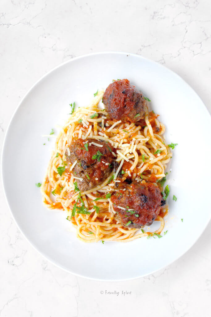 overhead view of a plate of spaghetti and meatballs with parmesan grated on top