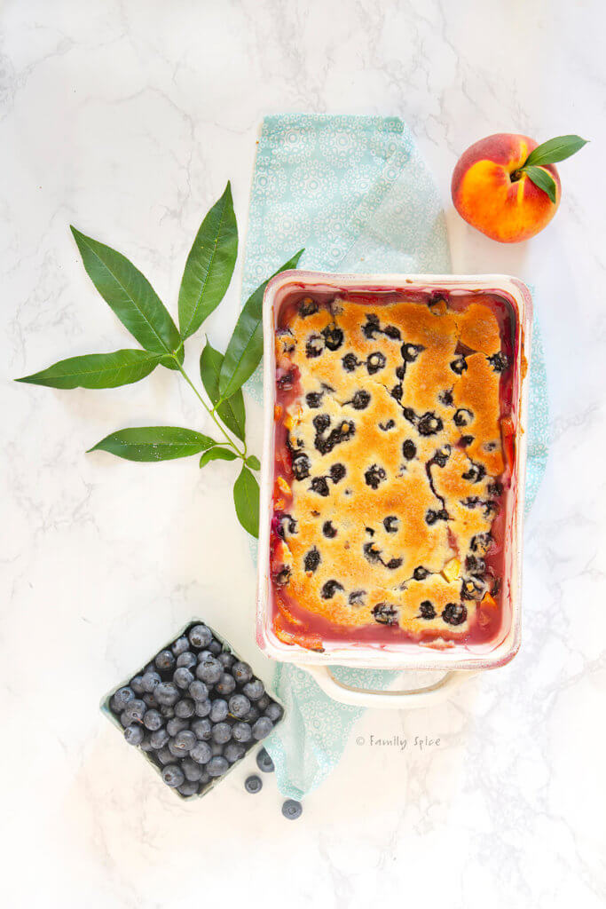 Freshly baked peach blueberry cobbler with a fresh peach and a basket of fresh blueberries