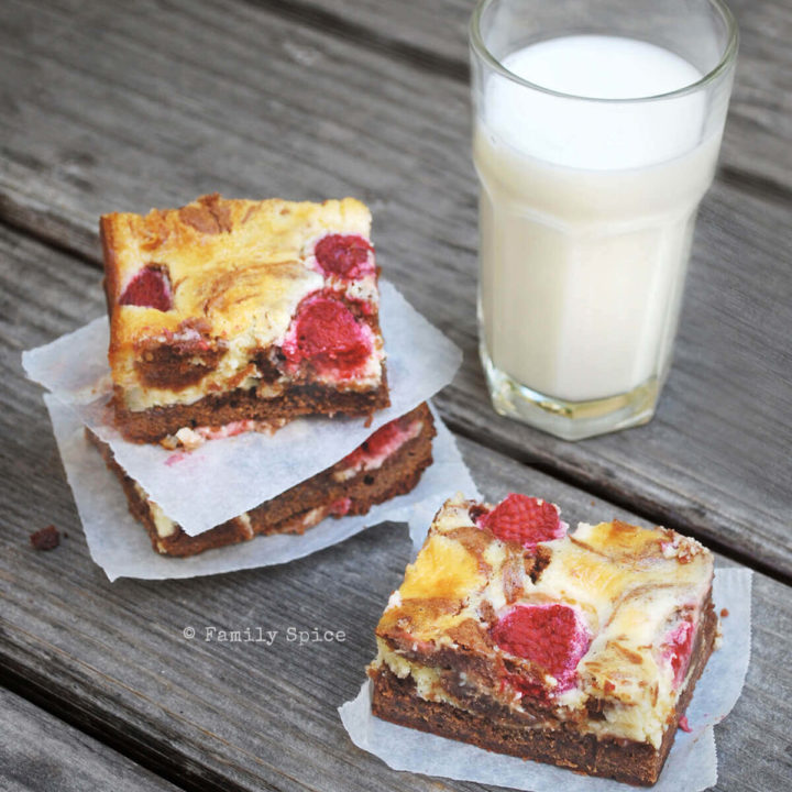 Slices of raspberry cheesecake brownies with a glass of milk