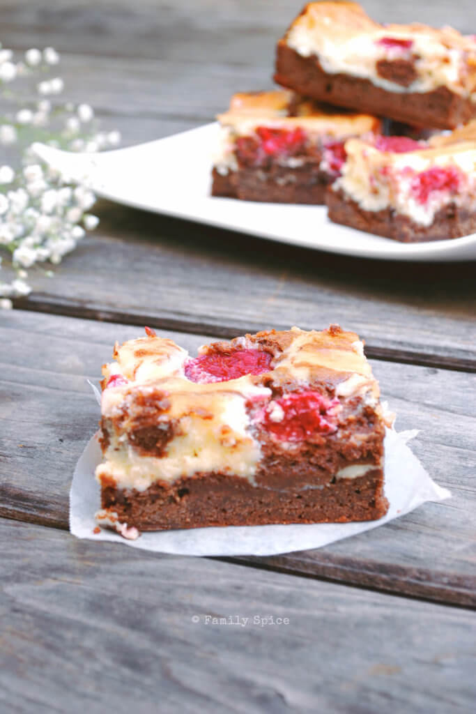 Closeup of a slice of raspberry topped cheesecake brownies
