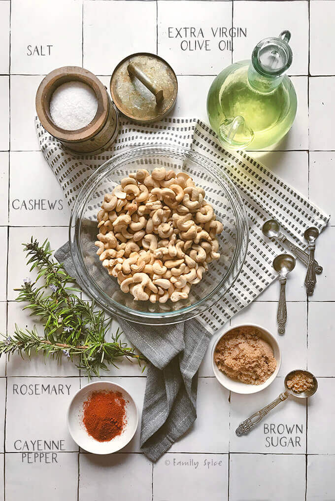Raw cashews in a bowl surrounded by rosemary, oil and seasonings