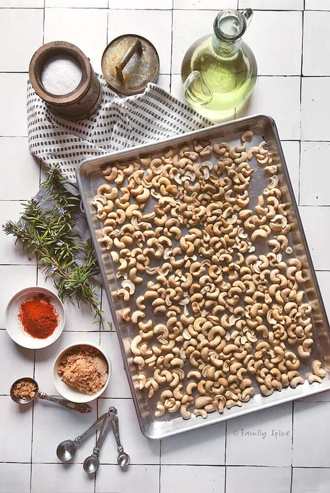 Raw cashews in a baking sheet surrounded by rosemary, oil and seasonings