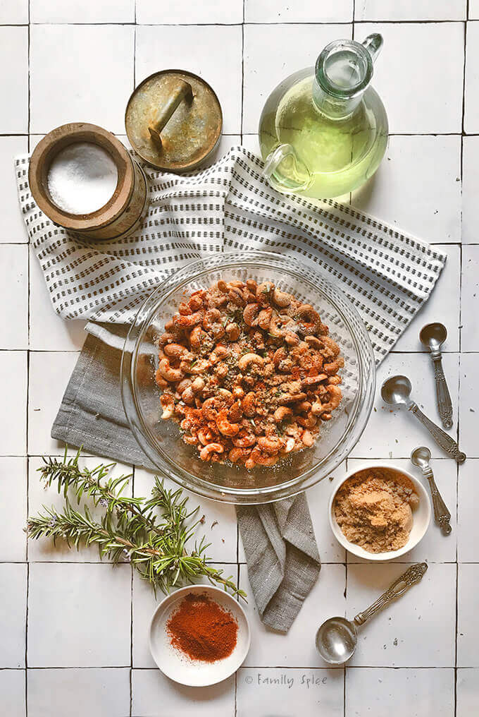 A bowl of roasted cashews in a bowl with seasonings on top and surrounded by rosemary, oil and seasonings