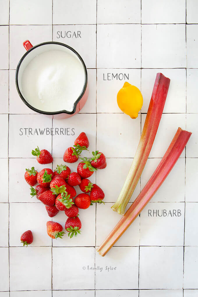 Ingredients to make strawberry rhubarb jam: sugar, lemon, rhubarb and strawberries