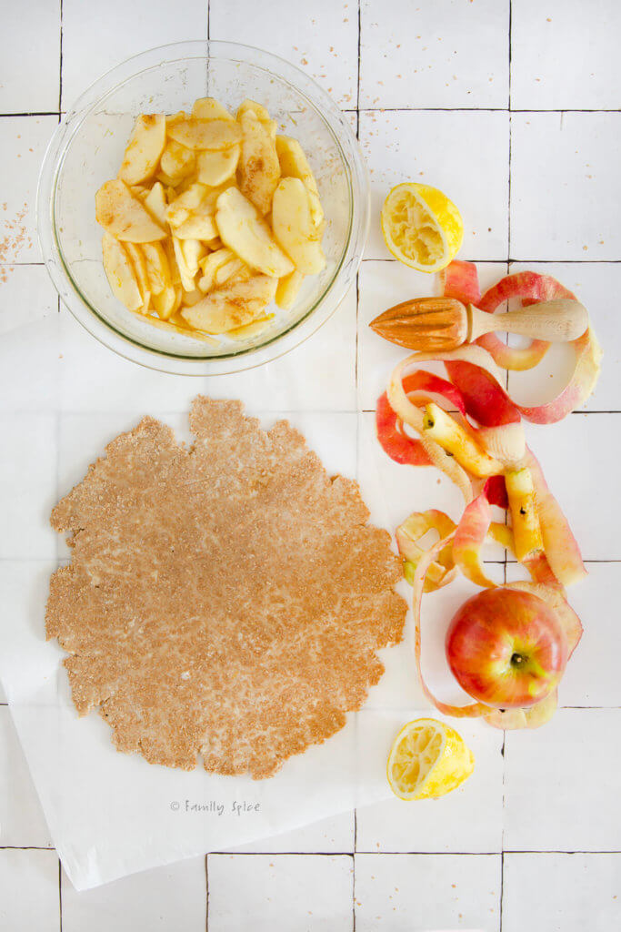 A whole wheat pie crust rolled flat with a bowl of prepared apple slices and apple peels next to it