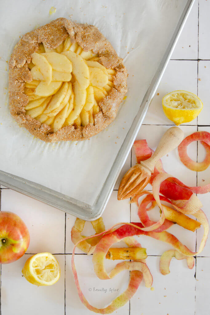A whole wheat galette crust with apple slices prepped and on a baking sheet ready to be baked