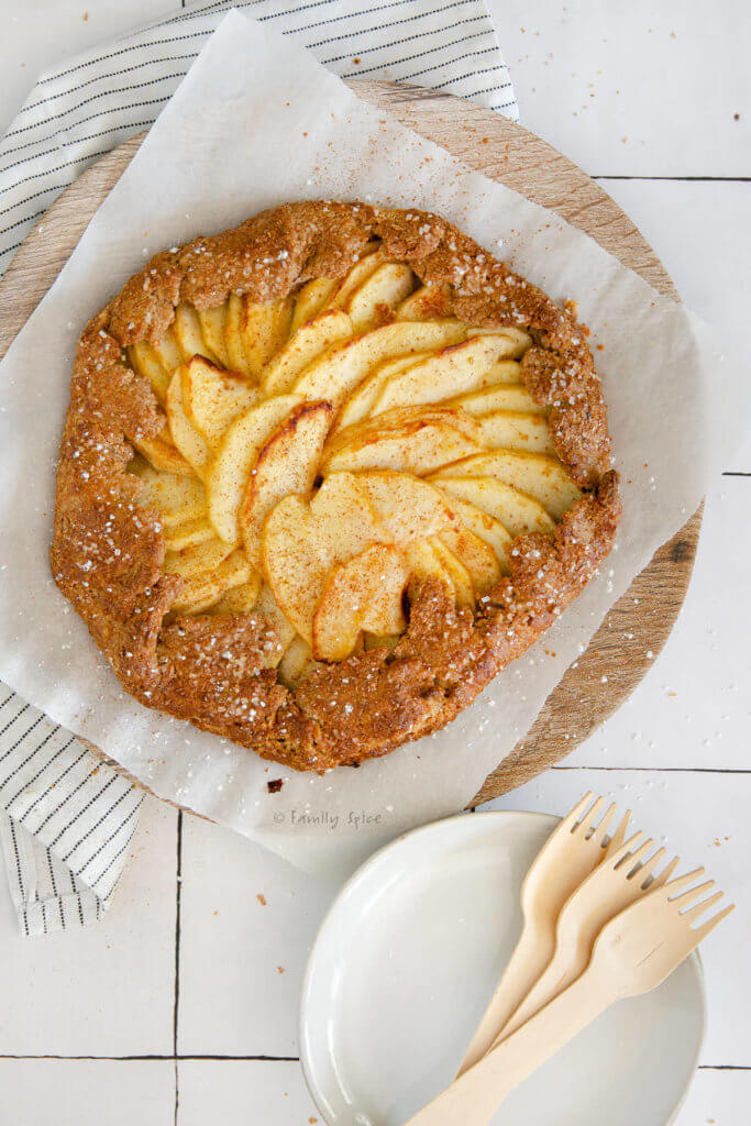 A freshly baked whole wheat apple galette with small white plates and bamboo forks